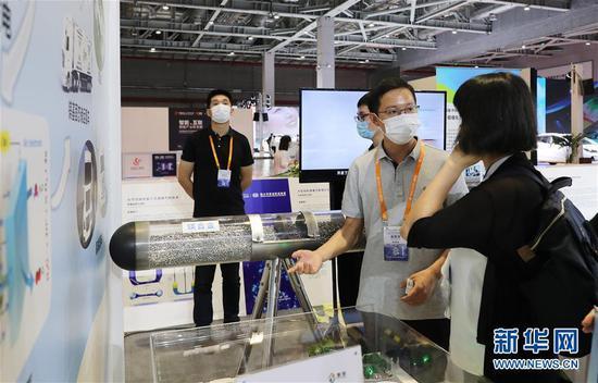 9月15日,工作人员(右二)向参观者介绍研究成果。新华社记者 方喆 摄