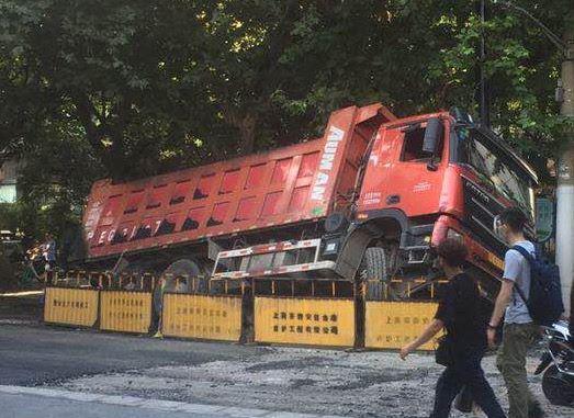 图说:静安区大田路靠近北京西路,因路面下陷,一辆卡车后轮陷入路面,险些侧翻 来源/网友提供
