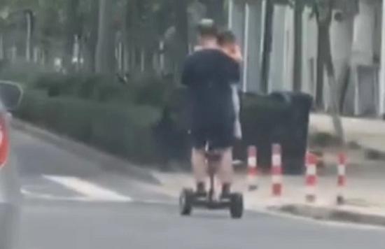 图说:一男子脚踩平衡车手里抱着娃 网友供图