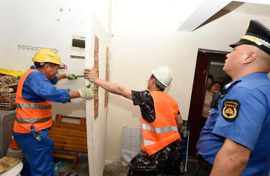 △执法人员当场拆除违规隔断房。