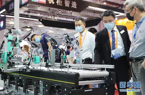 9月15日,一名展方工作人员(右二)向参观者介绍展品。新华社记者 方喆 摄