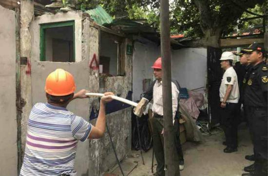 图说:虹口城管在拆除违法建筑。宏新摄(下同)