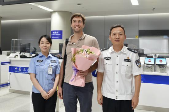 图说:上海机场边检站民警为卫星厅首位入境中转旅客送上鲜花。魏文亨 摄
