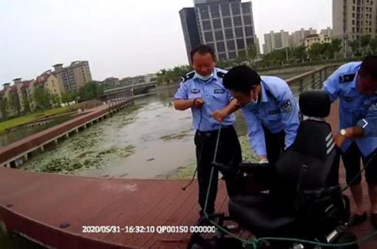 民警帮助打捞坠河的电动代步车。