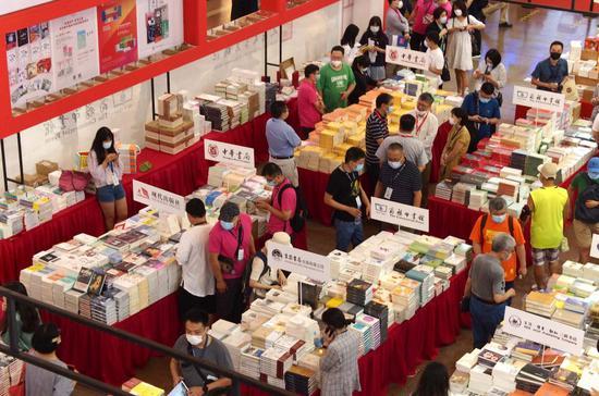 8月12日,读者在位于上海展览中心的2020上海书展主会场上选购图书。新华社记者 任珑 摄