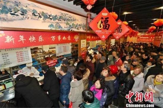 图说:民众排长队购熟食备年货。
