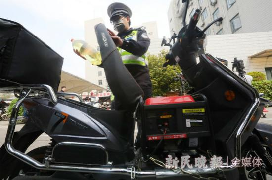 图说:民警从电瓶车座位下取出汽油。新民晚报记者 张龙 摄