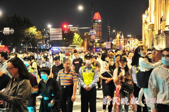图说:10月1日晚,外滩的执勤民警在人流中坚守岗位。杨建正 摄