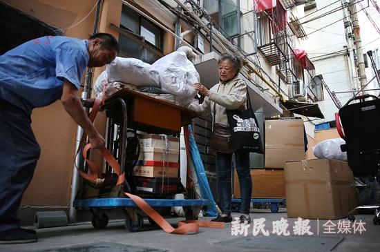 图说:家具和行李都搬到了楼下,杨建民扶着缝纫机看工人固定