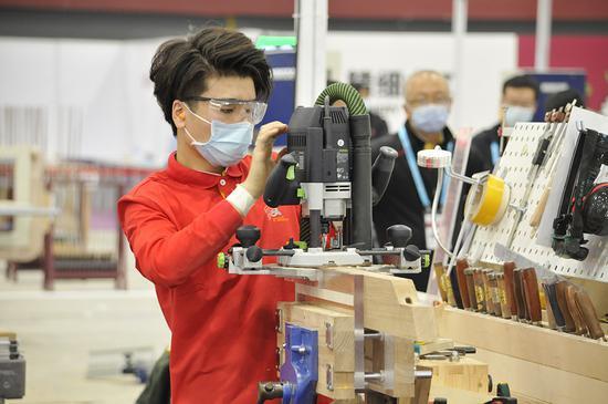 孙岩在精细木工比赛项目中操作显微镜