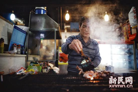 图说:50岁的安徽人王盈军对自创的烤牛蛙信心十足。新民网记者萧君玮 摄(下同)