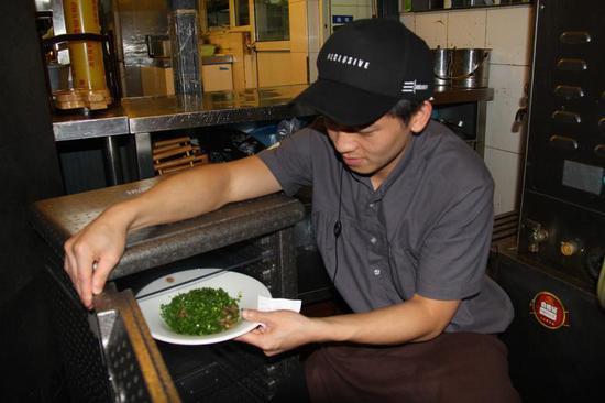 """等在合作饭店内的""""共享餐厅""""服务员将盖好保鲜膜的菜放入周转箱"""