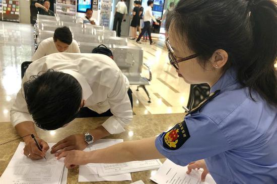 """6月29日上午,""""共享餐厅""""负责人在黄浦区市场监管局签字,领取食品经营许可证"""