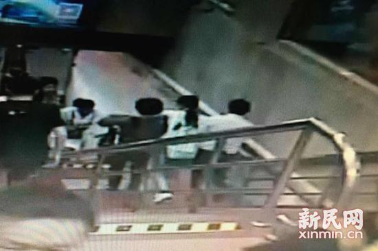图说:热心阿姨帮助站务员一同将身体不适乘客送往厕所。监控截图