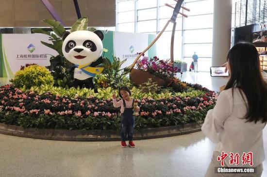 资料图:10月25日,上海虹桥机场,旅客在进博会吉祥物雕塑前合影留念。 中新社记者 殷立勤 摄