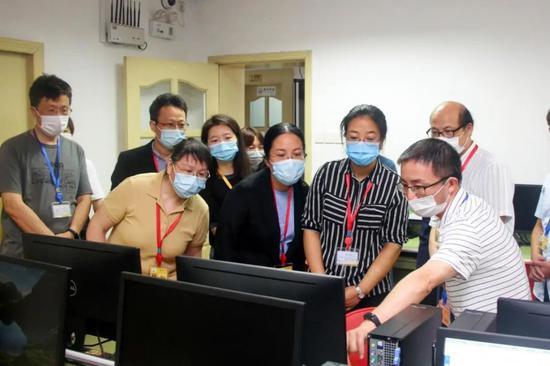 工作人员向考生家长介绍评卷技术保障和校验情况