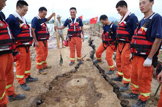 """2020年7月23日,抗洪前线安徽无为市黄埠村河段,上海消防队员们为队友康陈杰垒了一个""""泥土蛋糕""""。 受访者供图"""