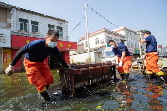 2020年8月7日,安徽省巢湖市柘皋镇,洪水退去后,上海消防员正在清淤。 上海消防 供图