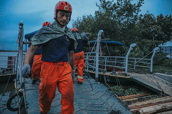 项青松在圩坝上装填搬运土袋。 受访者供图