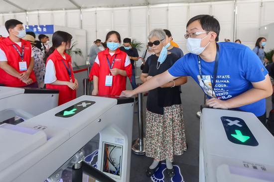 8月12日,工作人员帮助老人刷身份证实名认证入场。新华社记者 王翔 摄
