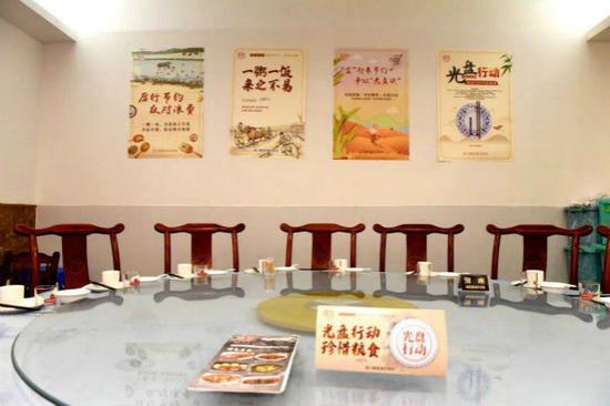"""图说:在餐饮店张贴关于""""宜起来""""节约宣传海报,倡导大家争当""""光盘族""""。街道供图"""