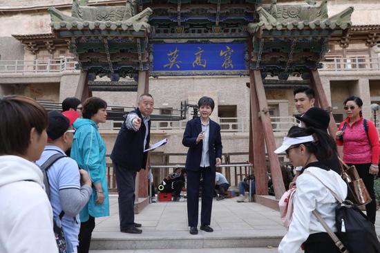 沪剧电影《敦煌女儿》拍摄现场,导演滕俊杰正在给演员讲戏