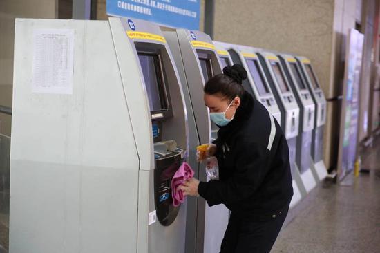工作人员对自助售取票机进行常规消毒。赵金爱 摄