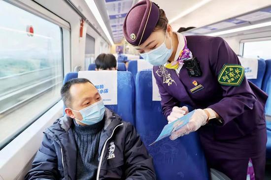 列车工作人员在车厢内加强防疫宣传。周围 摄
