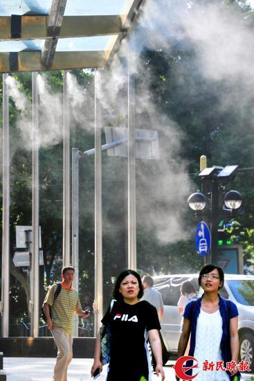"""图说:尽管已过处暑节气,早晚时段已渐凉,但申城白天街头行走的路人明显感到""""热度不减""""。 杨建正摄"""