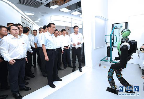 7月22日至23日,中共中央政治局常委、国务院总理李克强在上海考察。这是7月23日,李克强在上海张江人工智能岛察看3D视觉远程医疗、智能神经仿生、智能无人系列技术等创新成果。 新华社记者 饶爱民 摄