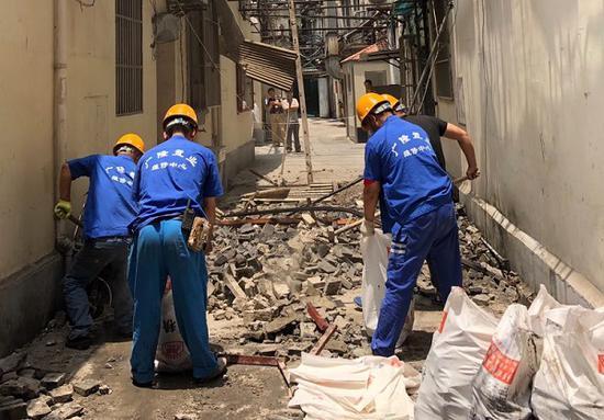 图说:工作人员正在清理坍塌的碎石 居民供图(下同)