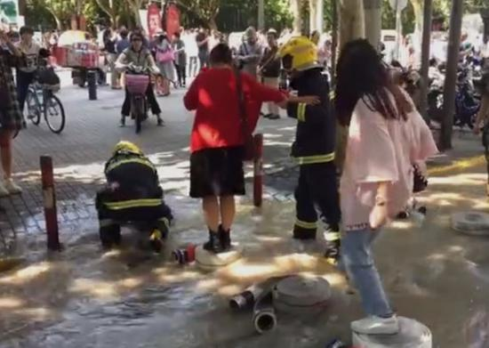 """图说:消防队员为行人铺设的临时""""小桥"""""""