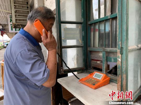 吕树生说,这个电话亭就像家里一样的,每天要到这里来。 康玉湛 摄