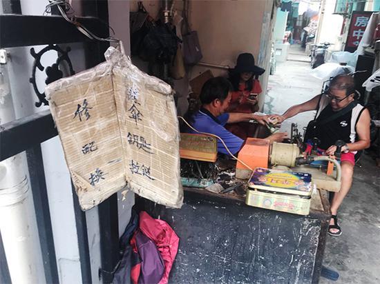 图说:修鞋摊摆在石库门过街楼下的一角。李一能 摄