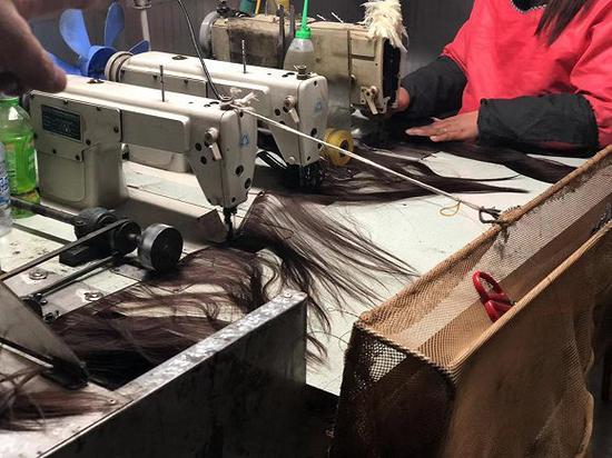 工人们正在把处理好的头发打成发片,方便下一步织到发网上。图片拍摄:刘雨静