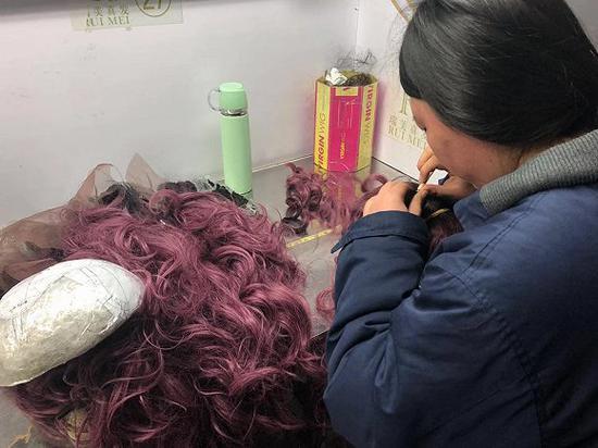正在将假发勾到发网上的工人。图片拍摄:刘雨静