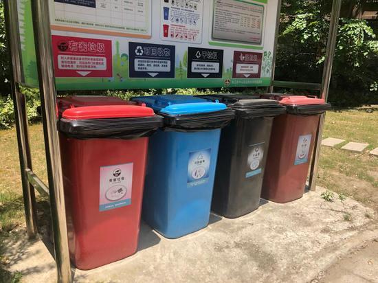 """小区的醒目位置,设立了配备四分类垃圾桶的""""垃圾分类收集亭"""""""