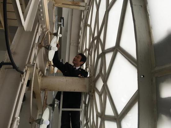 魏云寺今年元旦在钟楼检查大钟表面的灯源装置。(李晔 摄)