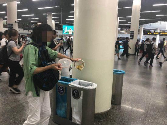 图说:女子将碗里的饭菜倒进了地铁站的垃圾桶内。劳动观察
