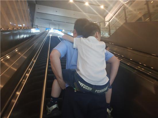 图说:民警刘宇翔背着沉睡的男孩上车,连夜冒雨将其送至户籍地派出所代为照顾。罗鹏飞 摄(下同)