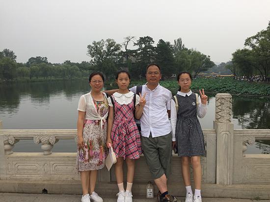 双胞胎姐妹全家福,从左到右依次为妈妈、金蒙璇、爸爸、金蒙璐。 受访者供图