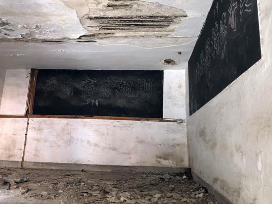 △两层的宿舍楼已风化严重。图为宿舍楼楼梯间内,头顶的水泥成了豆腐渣状,地上则全是掉下来的水泥块。