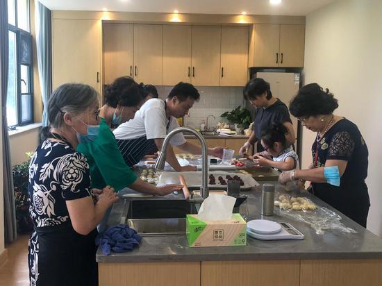 老人们在为老服务中心的烘焙坊学习制作鲜花饼。