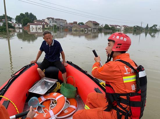 在鹤毛镇,项青松驾救生艇转移一位受困老人。 受访者供图