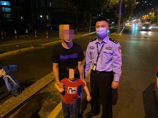 图说:幼童找到父亲后与民警合影