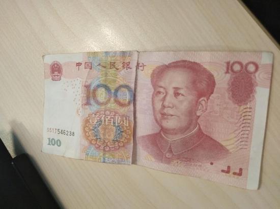 图说:被撕毁的百元人民币 受访者供图