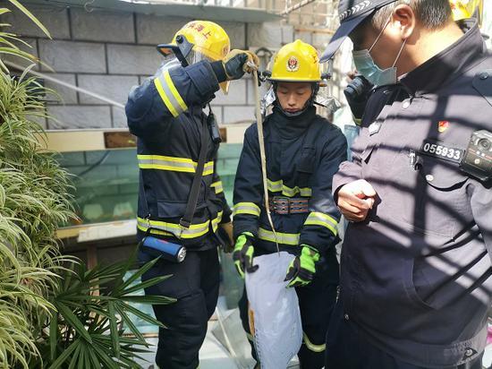 图说:消防队员成功捉蛇 来源/警方供图