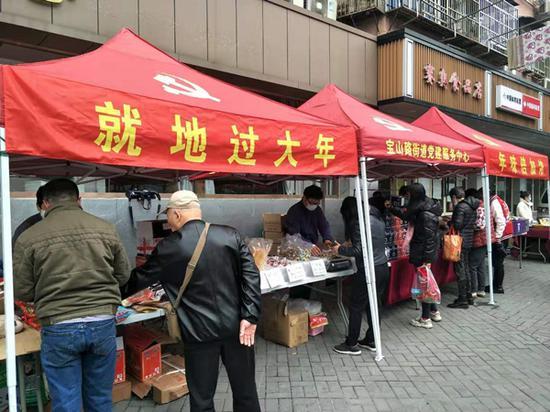 图说:一排红色大棚搭建在宝山社区党群中心的门口,为留沪外来务工人员节日期间购买年货提供便利 采访对象供图(下同)