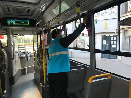 工作人员在沿途经过市北中学的公交车上擦拭、消毒。受访者供图