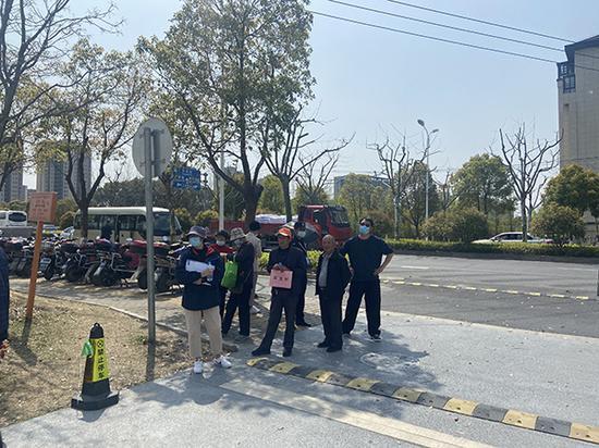 上海青浦区体育文化中心外围,相关人员拿着牌子等待接送疫苗接种人员。 本文图均为澎湃新闻记者 巩汉语 图